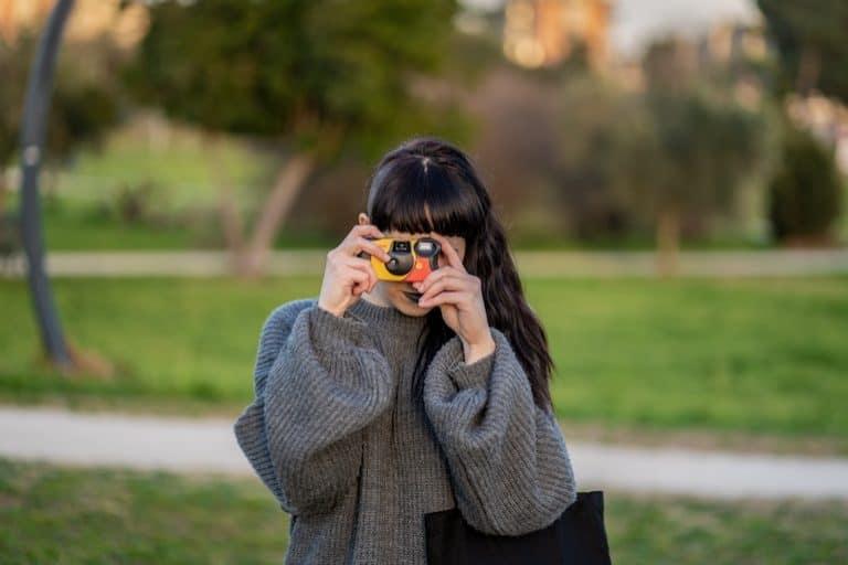 Frau macht Bild mit Einwegkamera