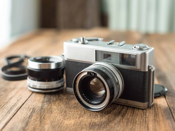 Old retro Film camera on wooden background that had been popular in the past