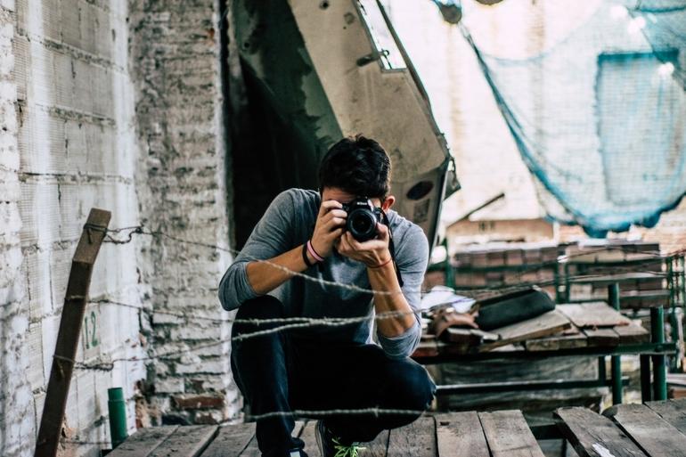 Ein junger Mann fotografiert mit einer Systemkamera.